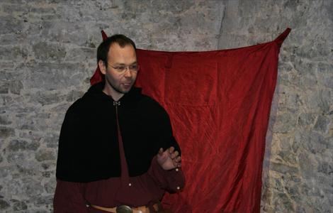 David en costume médiéval devant un public